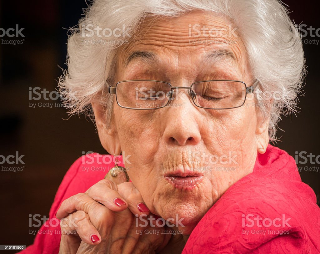 Senior woman with playful, mischievous, facial expression stock photo