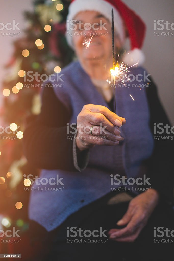 senior woman with santa hat and sparklers on christmas stock photo
