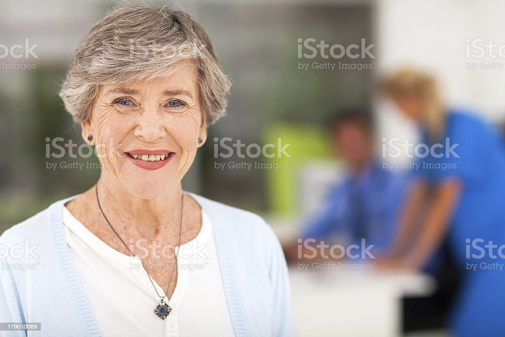 Senior woman with short hair smiling in doctors office stock photo