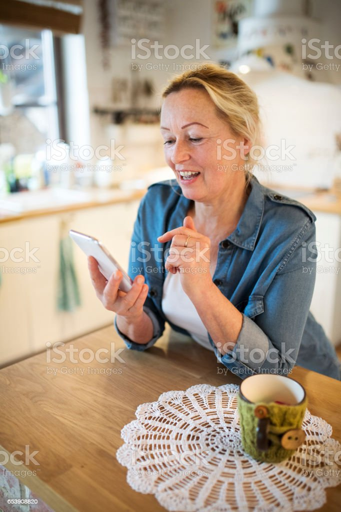 Senior woman with smartphone at home sitting in the kitchen stock photo