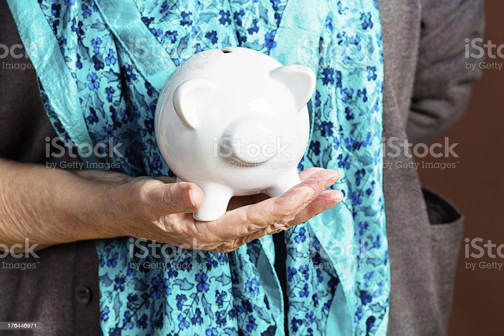 Senior woman with tiny nest egg in piggybank royalty-free stock photo