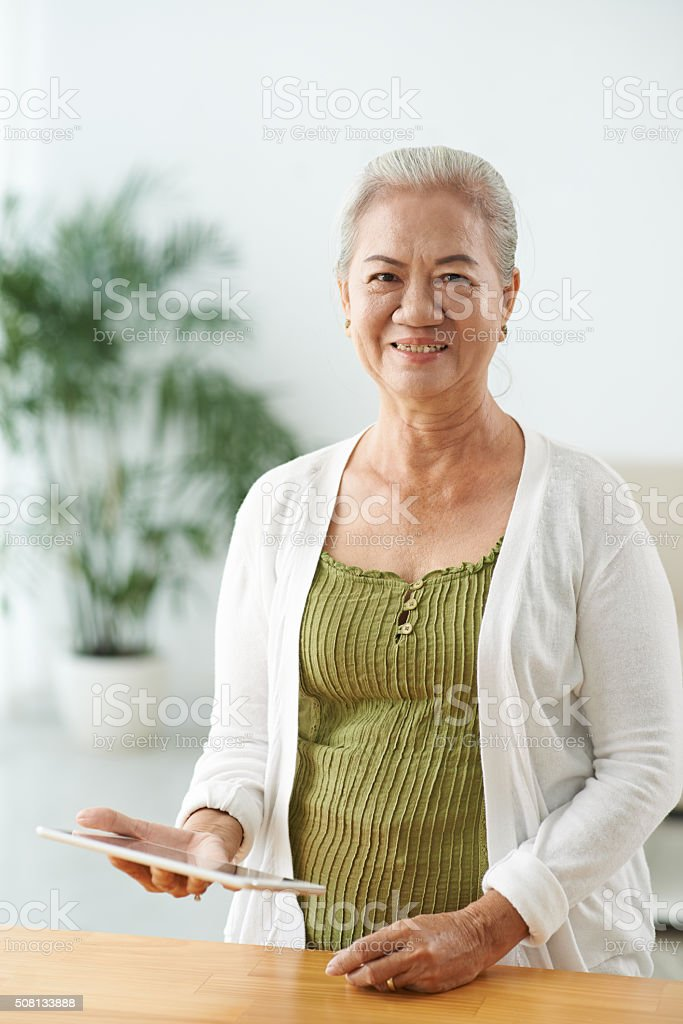 Senior woman with touchpad stock photo