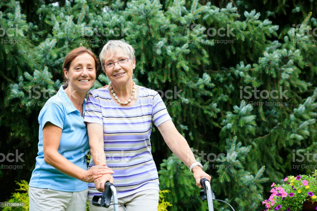 Senior woman with walker and caregiver royalty-free stock photo