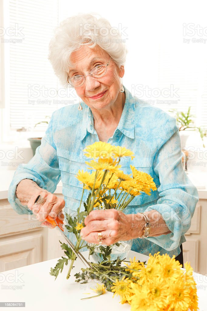 senior woman with yellow cut flowers royalty-free stock photo