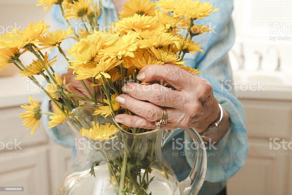 senior woman with yellow cut flowers stock photo