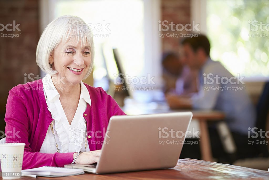 Senior Woman Working At Laptop In Contemporary Office royalty-free stock photo