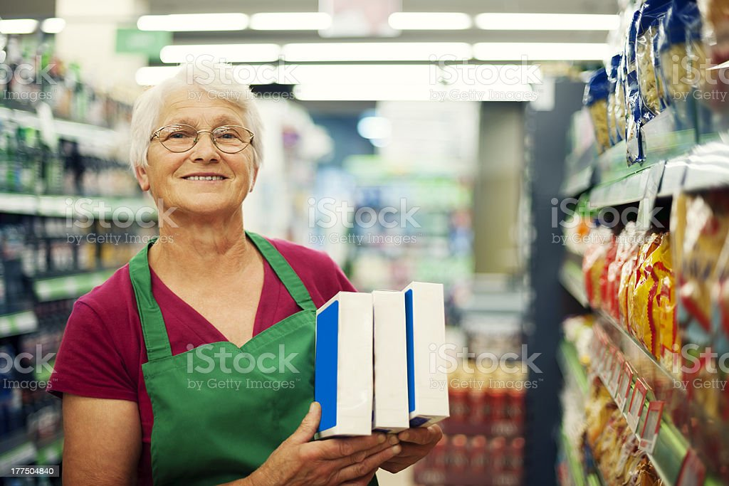 Senior woman working at supermarket stock photo
