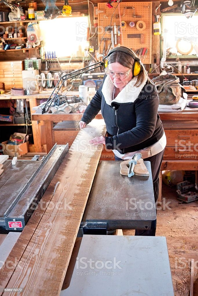 Senior woman working in a wood shop. stock photo