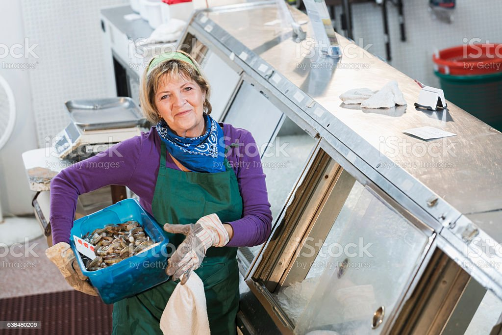 Senior woman working in fish market stock photo