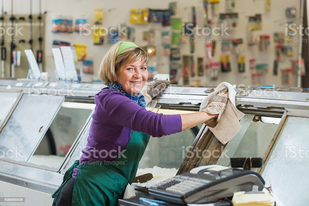 Senior woman working in fish market stock photo