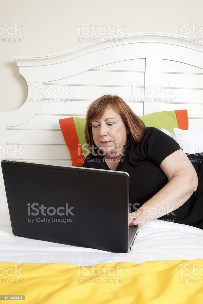 Senior woman working on laptop laying in bed royalty-free stock photo