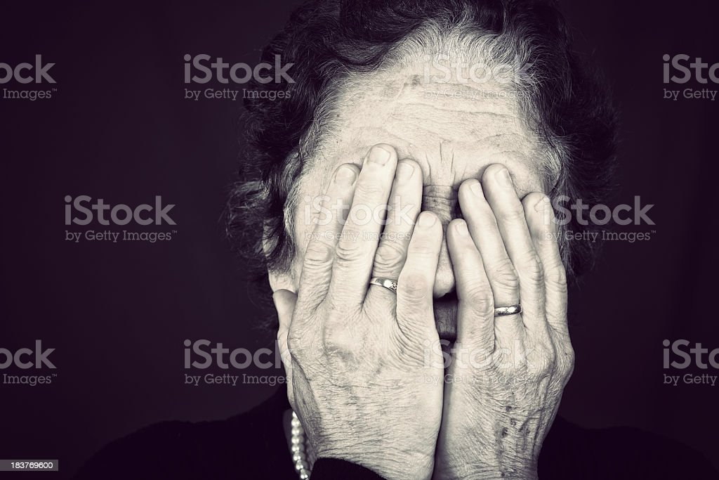 Senior woman worn hands covering face stock photo