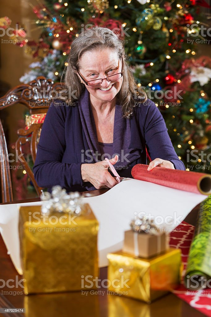Senior woman wrapping Christmas presents by tree stock photo