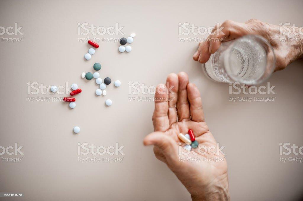 Senior Woman Wrinkled Hands Choosing Medicine To Take stock photo