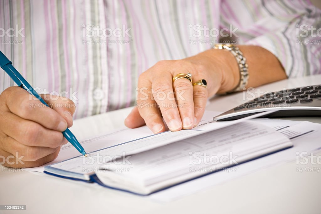Senior woman writing in her checkbook stock photo