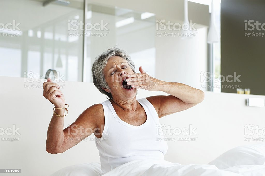 Senior woman yawning in bed stock photo
