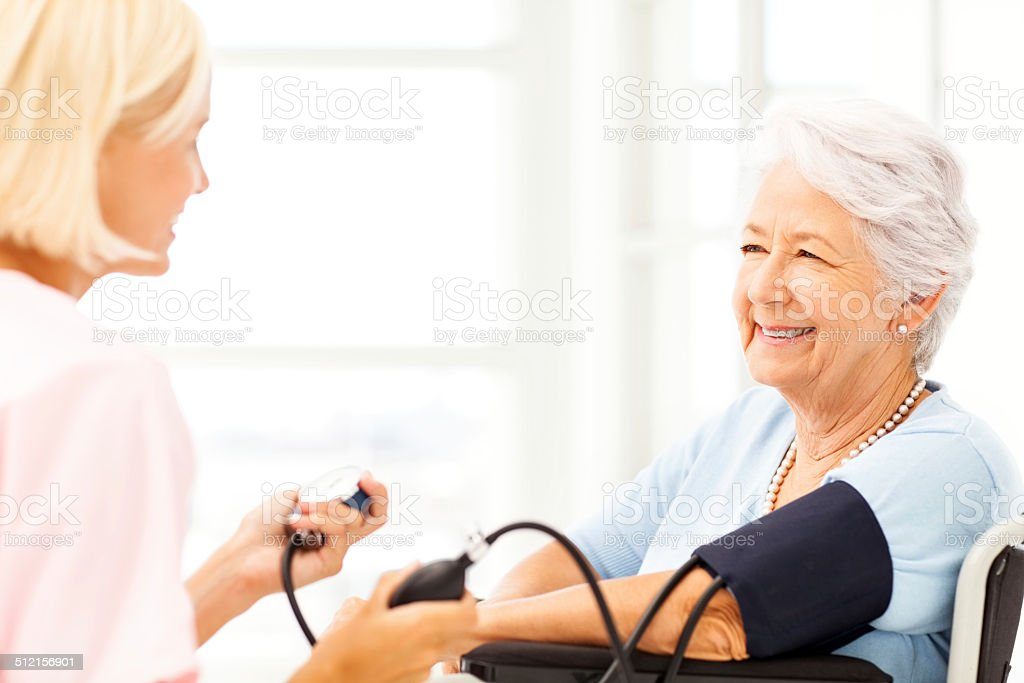 Senior Woman's Blood Pressure Being Measured By Nurse stock photo