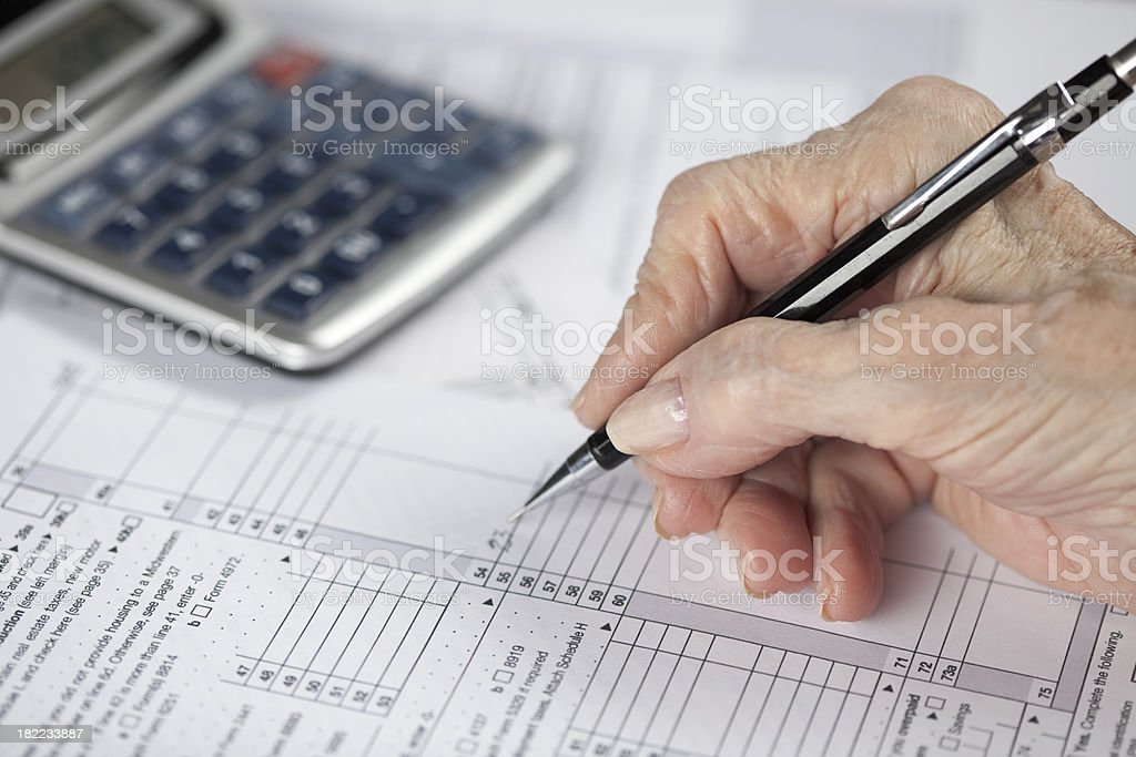 senior woman's hand doing financial paperwork stock photo