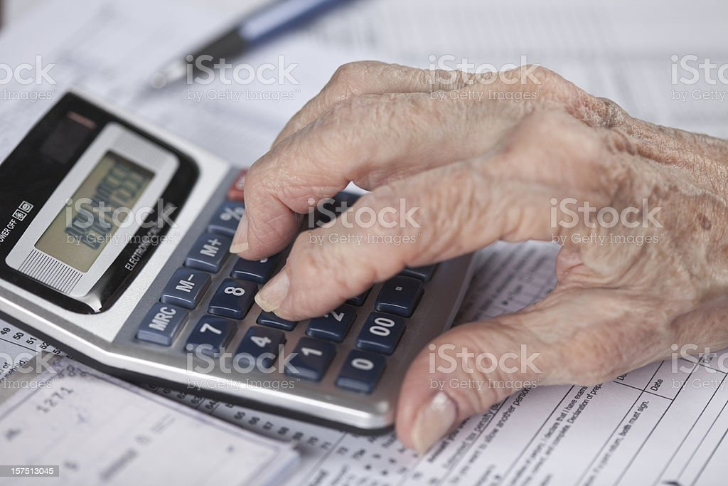 senior woman's hand doing financial work with calculator stock photo