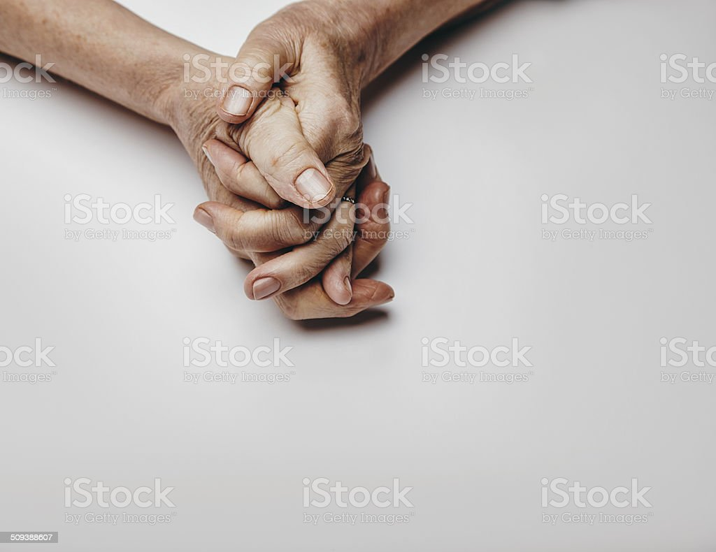 Senior woman's hands on grey background stock photo