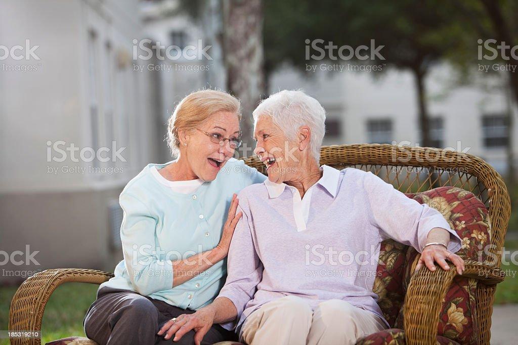 Senior women chatting on patio stock photo