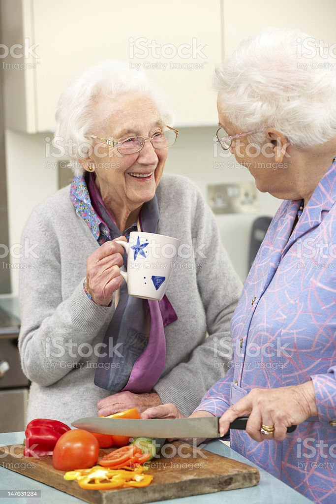 Senior women chopping vegetables together royalty-free stock photo