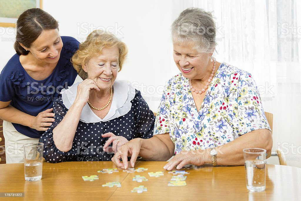 Senior women couple assembling a jigsaw puzzle royalty-free stock photo