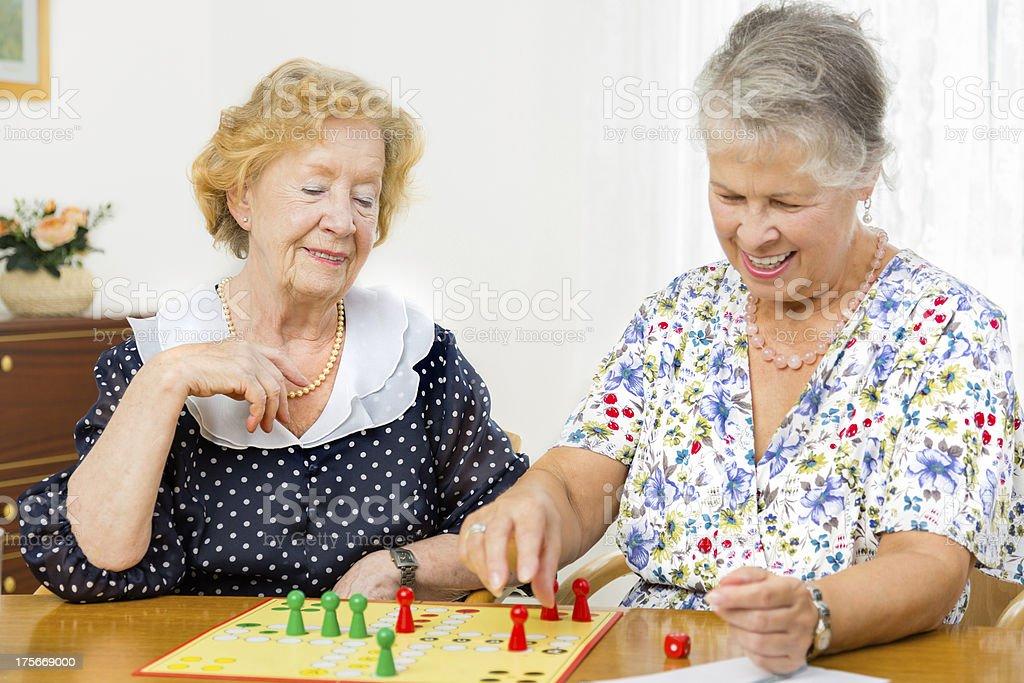 Senior women couple playing board game ludo royalty-free stock photo