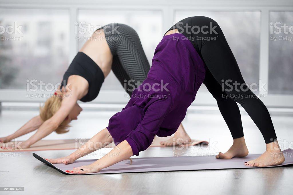 Senior women doing Downward-facing dog pose stock photo