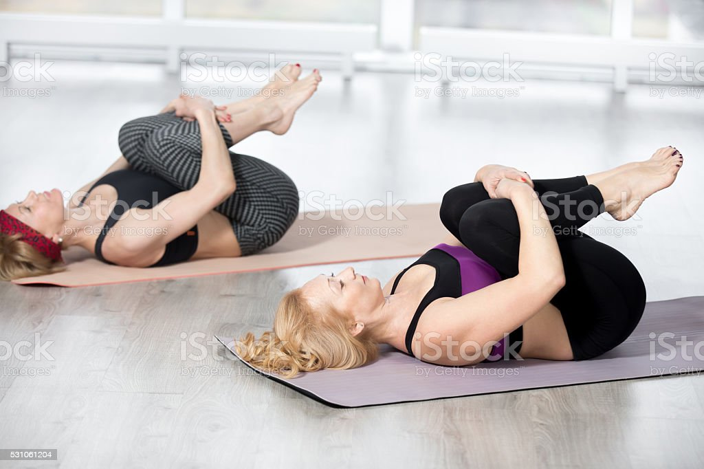 Senior women doing Knees to Chest Pose stock photo