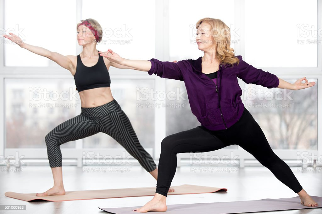 Senior women doing Warrior 2 Pose stock photo