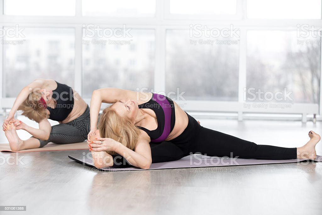 Senior women doing Wide-Angle Seated Forward Bend pose stock photo