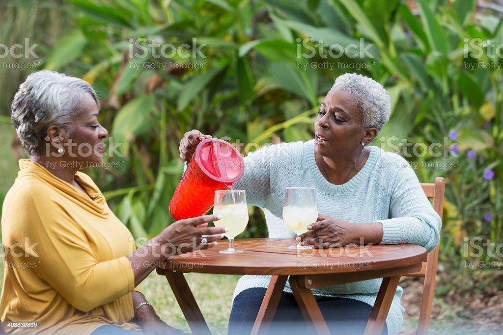 Senior women drinking lemonade together stock photo