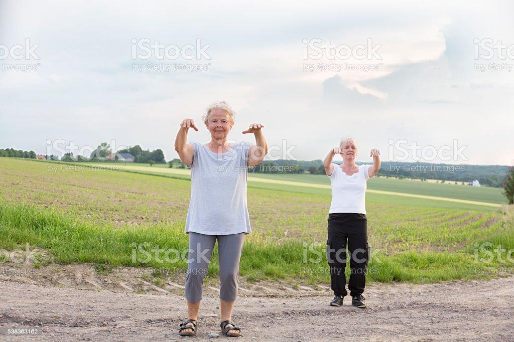 senior women exercising outdoors in summer stock photo