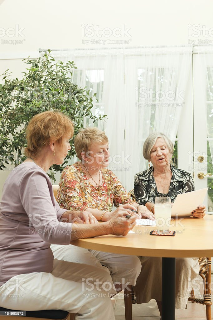 Senior Women Group Doing Paper Work Together in Social Gathering royalty-free stock photo