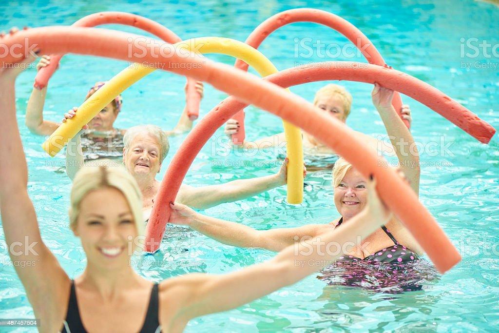 senior women led by female instructor at water aerobics stock photo