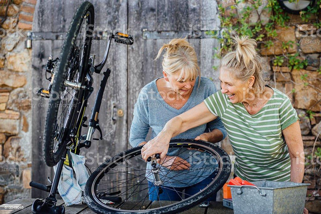 Senior Women Repairing a Bicycle stock photo
