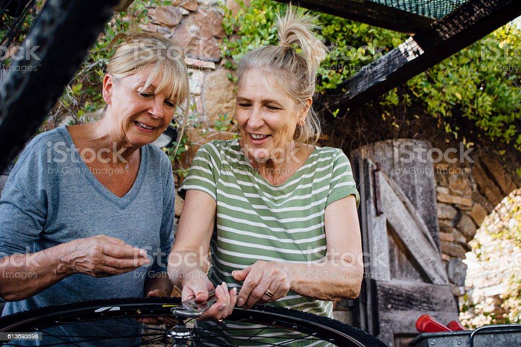 Senior Women Repairing a Bicycle Wheel stock photo