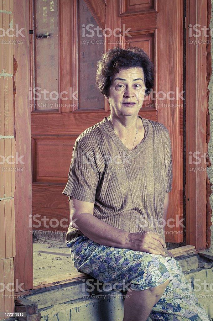 Senior women sitting on the door royalty-free stock photo