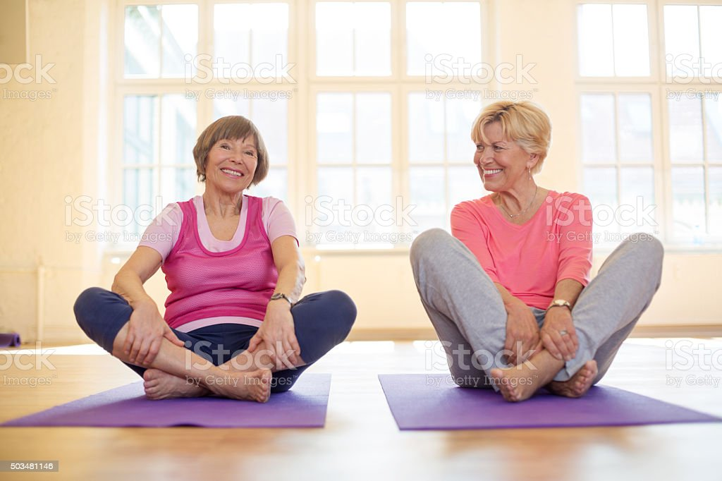 Senior women sitting on yoga mat with their legs crossed stock photo