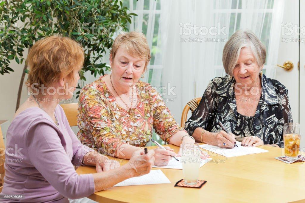 Senior Women Socializing in Lounge Doing Paper Work at Senior Care Center stock photo