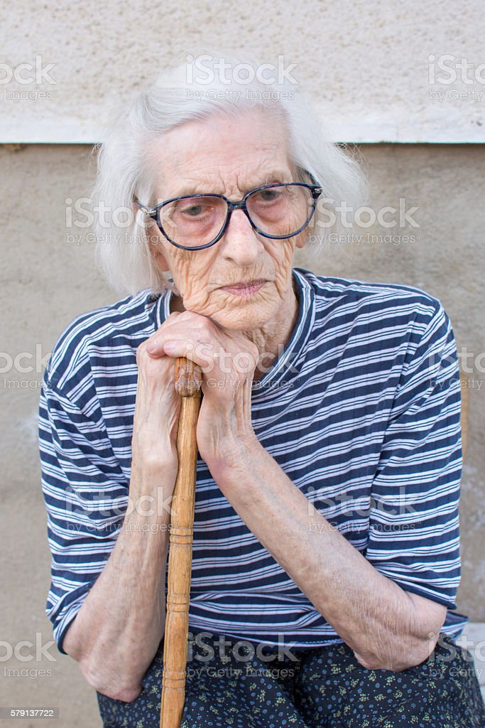 Senior women supporting on a walking cane stock photo