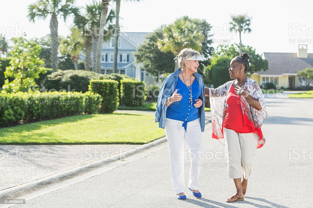 Senior women taking a walk on a sunny day, laughing stock photo
