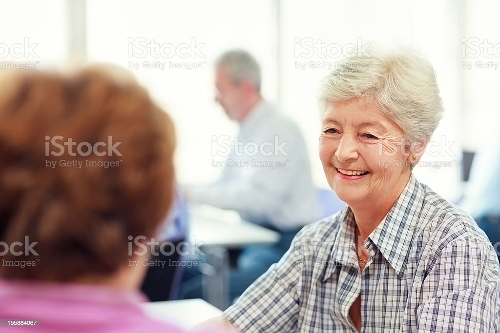 Senior women talking in community center stock photo