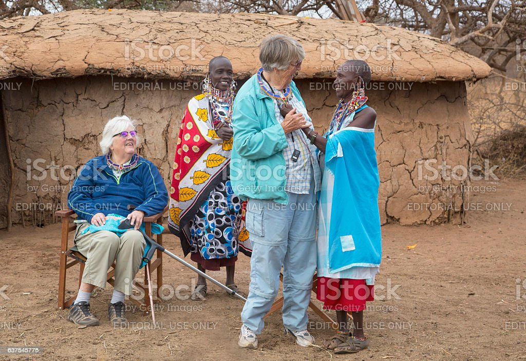 Senior women, tourists and Maasai arranging pearl jevellry. stock photo