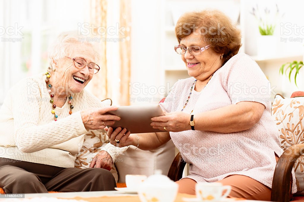 Senior women using together a digital tablet royalty-free stock photo