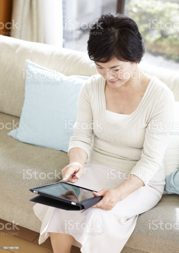 Senior women working with Tablet PC stock photo