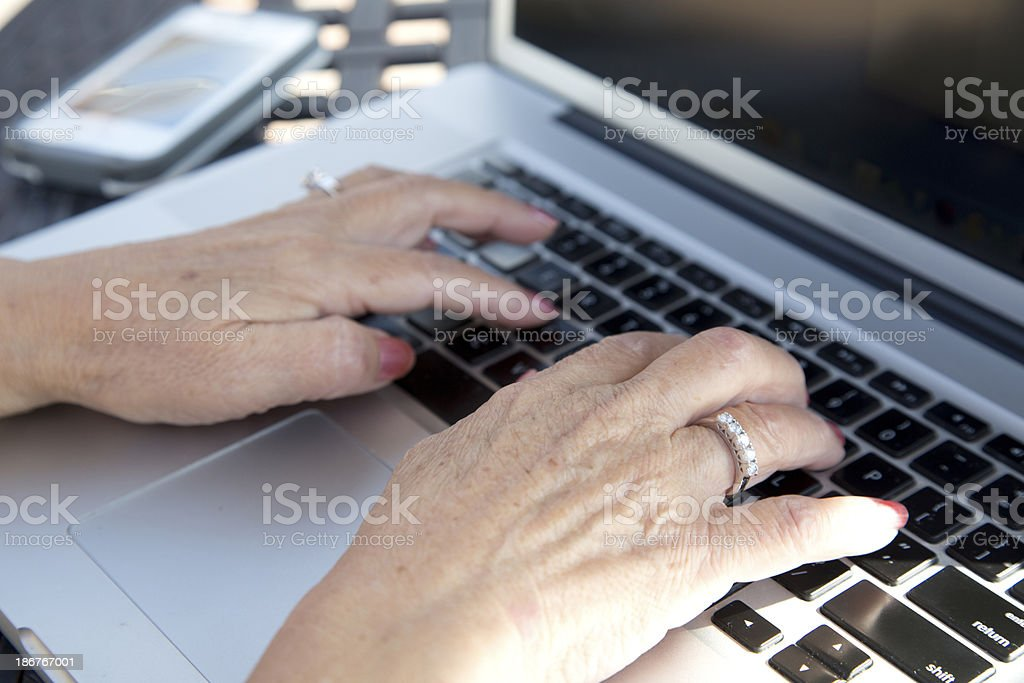 Senior Womens Hands on Laptop with Cell Phone royalty-free stock photo