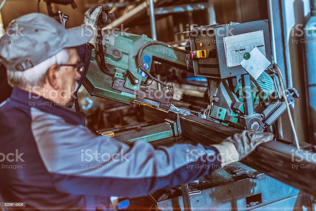 Senior worker operating a steel-cutting machine stock photo