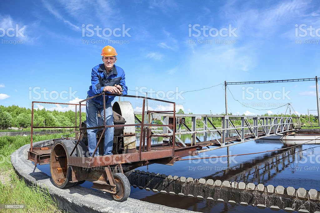 Senior worker standing on waste water treatment unit stock photo